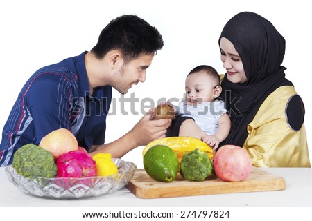 Portrait of happy father giving a fresh fruit to his little son, isolated on white background