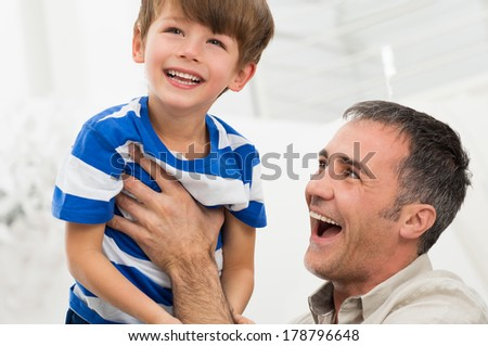 Portrait Of Happy Father Raises His Son In The Air - stock photo