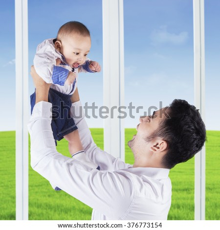 Portrait of happy father standing near the window while holding an adorable male baby at home - stock photo