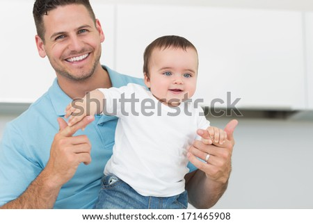 Portrait of happy father with cute baby boy at home - stock photo