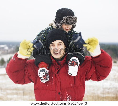portrait of happy father with his son outside in winter landscape, lifestyle people concept, real family together
