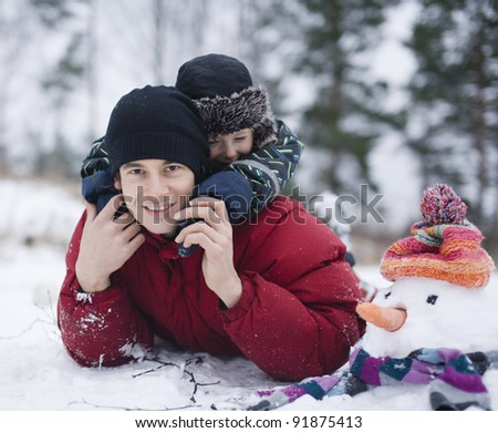 portrait of happy father with his son outside with snowman