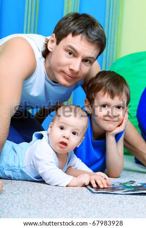 Portrait of happy father with his two son at home. - stock photo