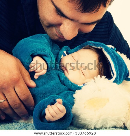 Portrait of happy father with sleeping little kid - stock photo
