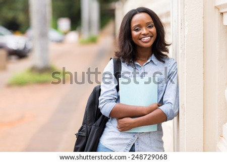 portrait of happy female african american college student holding a book - stock photo