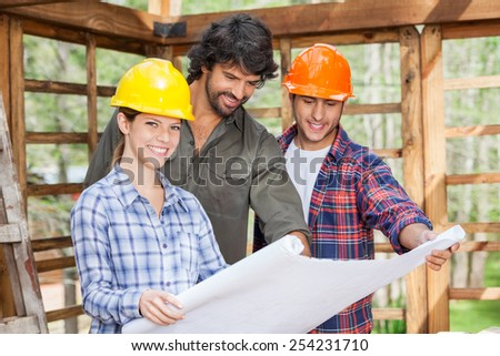 Portrait of happy female architect examining blueprint with male colleagues in wooden cabin at site