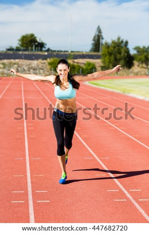 Portrait of happy female athlete running with arms outstretched