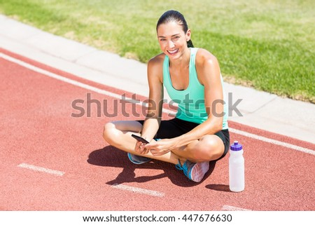 Portrait of happy female athlete using mobile phone on running track - stock photo