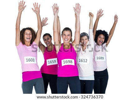 Portrait of happy female athletes with arms raised while standing against white background