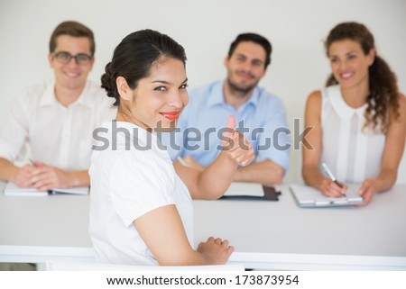 Portrait of happy female candidate gesturing thumbs up with interviewers in background - stock photo