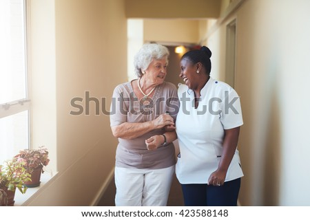 Portrait of happy female caregiver and senior woman walking together at home. Professional caregiver taking care of elderly woman. - stock photo