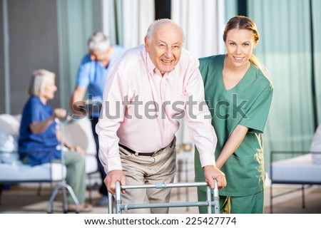 Portrait of happy female caretaker helping senior man in using Zimmer frame at nursing home yard - stock photo