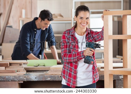 Portrait of happy female carpenter drilling wood while colleague working in background at workshop - stock photo