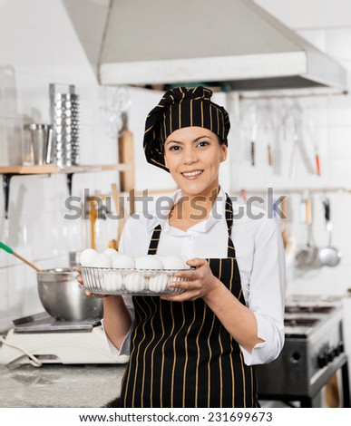 Portrait of happy female chef holding container full of eggs in commercial kitchen