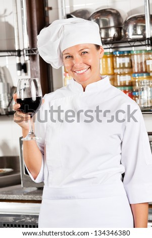 Portrait of happy female chef holding glass of red wine at commercial kitchen - stock photo