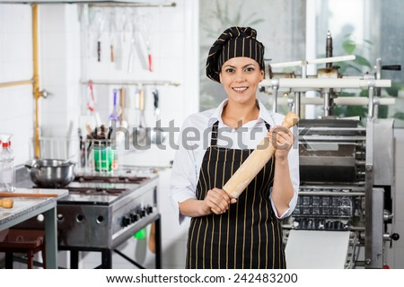 Portrait of happy female chef holding rolling pin in commercial kitchen - stock photo