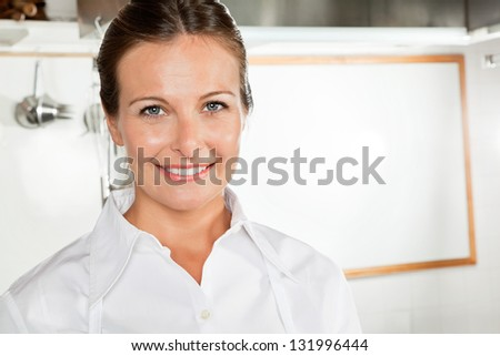 Portrait of happy female chef in industrial kitchen - stock photo