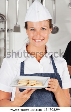 Portrait of happy female chef presenting cookies in industrial kitchen - stock photo