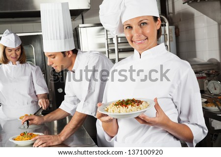 Portrait of happy female chef presenting pasta with colleagues in background - stock photo