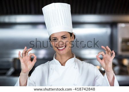 Portrait of happy female chef showing ok sign in commercial kitchen - stock photo