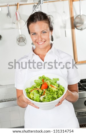 Portrait of happy female chef showing vegetable salad in industrial kitchen - stock photo
