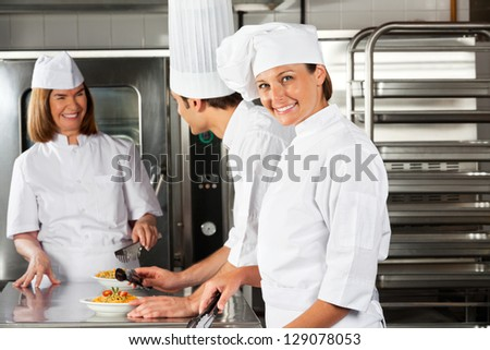 Portrait of happy female chef with colleagues communicating in background at commercial kitchen