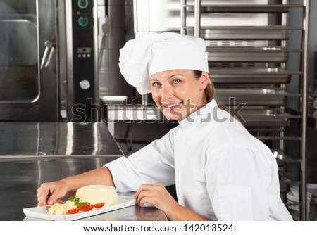 Portrait of happy female chef with dish at kitchen counter - stock photo