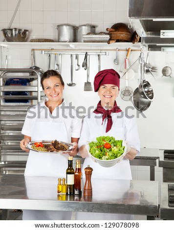 Portrait of happy female chefs with their dishes standing at kitchen counter - stock photo