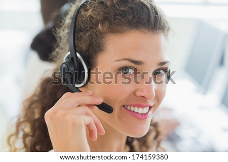 Portrait of happy female customer service agent using headset in call center - stock photo