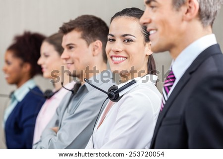 Portrait of happy female customer service representative standing with colleagues and manager at call center - stock photo