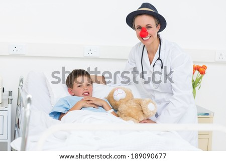 Portrait of happy female doctor in clown costume with sick boy in hospital bed