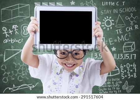 Portrait of happy female elementary school student standing in the class while showing empty tablet screen - stock photo