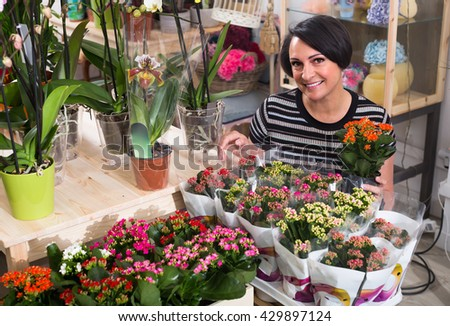 Portrait of happy female florist arranging a kalanchoe calandiva in the gardening department