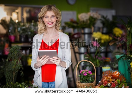 Portrait of happy female florist holding digital tablet in flower shop