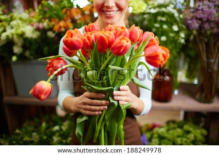 Portrait of happy female florist with bunch of red tulips looking at camera