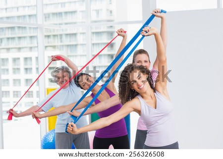 Portrait of happy female friends exercising with resistance bands in gym - stock photo