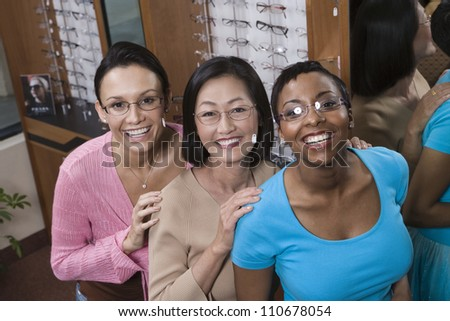 Portrait of happy female friends trying on glasses at optometrist