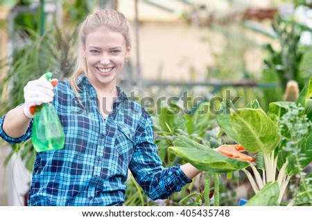 portrait of happy female gardener in greenhouse