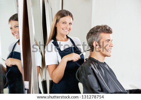 Portrait of happy female hairdresser cutting client's hair at salon - stock photo