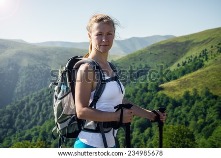 Portrait of happy female hiker wearing backpack.  - stock photo