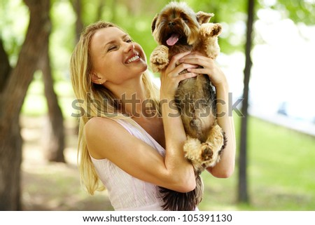 Portrait of happy female holding pet and looking at it in park - stock photo
