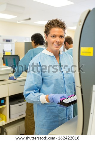 Portrait of happy female medical lab tech with sample for coagulation analysis - stock photo
