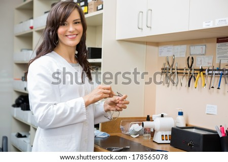Portrait of happy female optician repairing glasses with screwdriver in workshop - stock photo