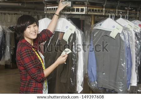 Portrait of happy female owner holding receipt by clothes rail in laundry - stock photo
