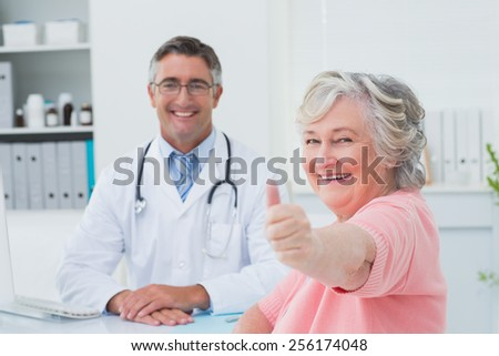 Portrait of happy female patient showing thumbs up sign while sitting with doctor in clinic - stock photo