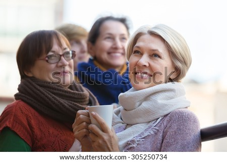 Portrait of happy female pensioner friends drinking coffee at patio. Focus on blonde - stock photo