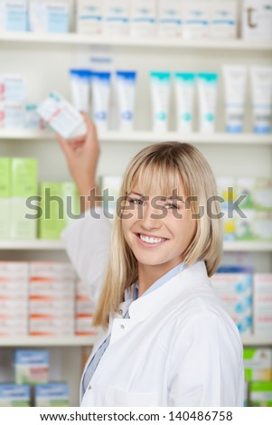 Portrait of happy female pharmacist taking medicine box from shelf at pharmacy - stock photo