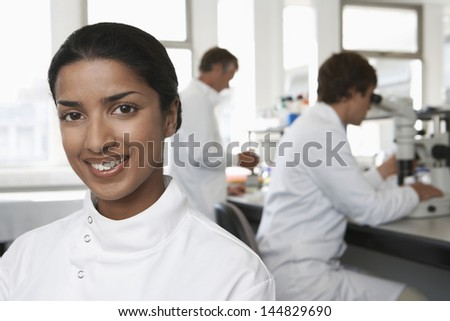 Portrait of happy female scientist with colleagues working in background - stock photo