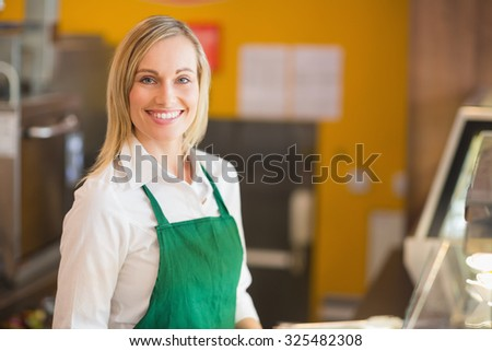 Portrait of happy female shop owner at counter in bakery - stock photo