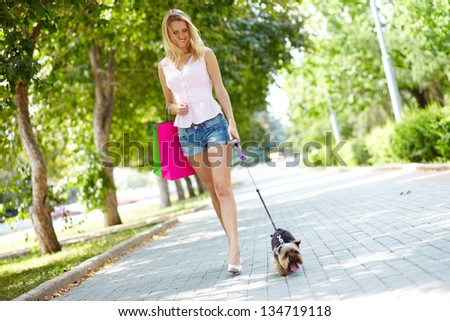 Portrait of happy female strolling with her pet at leisure - stock photo
